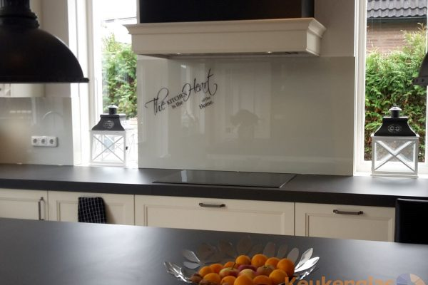 Witte spatwand glas met tekst The kitchen is the heart of the home