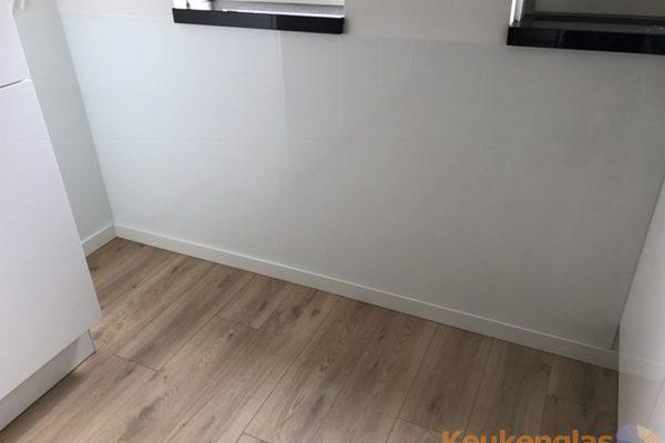 Witte glasplaat onder raam in keuken